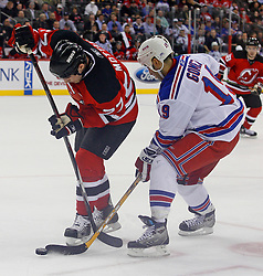 February 1, 2008; Newark, NJ, USA;  New Jersey Devils defenseman Mike Mottau (27) and New York Rangers center Scott Gomez (19) battle for the loose puck during the first period at the Prudential Center in Newark, NJ.