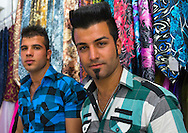Iran, Kermanshah, Young men with spiky haircut in the bazaar. Spiked hair has reportedly been banned in Iran because it implies devil-worship.
