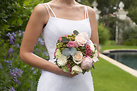 Mid adult bride at poolside holding bouquet mid section