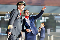 Young attractive stewardess pointing aircraft with the pilot in airport