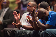 Adrian Taylor (blue) bows his head during a memorial service for his son Christian Taylor at Cornerstone Baptist Church in Arlington, Texas on August 12, 2015. (Cooper Neill for The New York Times)