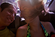 A couple of people (one hispanc and the other caucasian) looks each other in the back sit of a car.