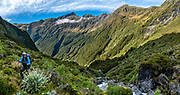 Tramping at the head of Young Valley. The Gillespie Pass Circuit follows the Young and Wilkin Rivers in Mount Aspiring National Park, in the Southern Alps. Makarora, Otago region, South Island of New Zealand. This image was stitched from multiple overlapping photos.