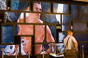 Fragrance male model advertising images on screen matrix at World of Duty Free at Heathrow's Terminal 5.