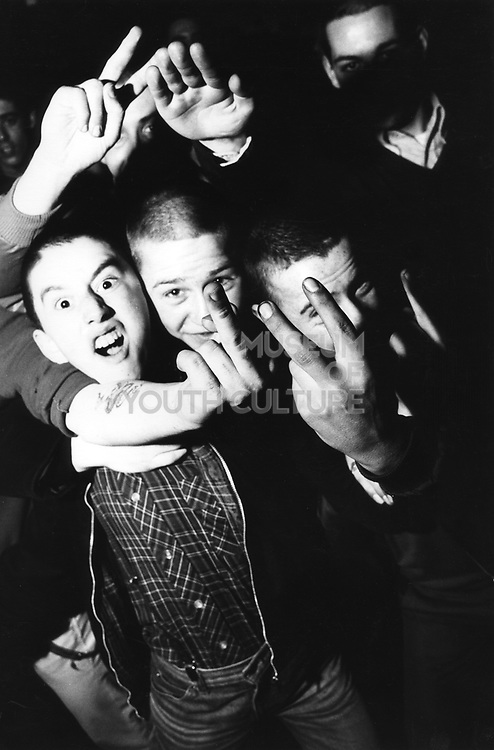 A group of rowdy skinheads, sticking their fingers up, One giving a Nazi salute, UK, 1980's.
