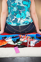Woman sitting on overstuffed suitcase mid section back view