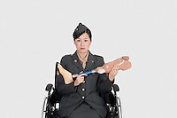 Female US military officer in wheelchair holding artificial limb over gray backgrounds