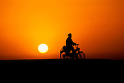 Red-gold sunset near the village of Kouakourou, Mali, Africa. This man has come from a neighboring village to the Saturday market on his motorbike. From coverage of revisit to Material World Project family in Mali, 2001.