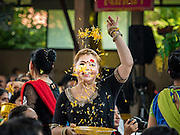 20 SEPTEMBER 2015 - SARIKA, NAKHON NAYOK, THAILAND: A woman throws marigolds while dancing at the Ganesh festival at Shri Utthayan Ganesha Temple in Sarika, Nakhon Nayok. Ganesh Chaturthi, also known as Vinayaka Chaturthi, is a Hindu festival dedicated to Lord Ganesh. Ganesh is the patron of arts and sciences, the deity of intellect and wisdom -- identified by his elephant head. The holiday is celebrated for 10 days. Wat Utthaya Ganesh in Nakhon Nayok province, is a Buddhist temple that venerates Ganesh, who is popular with Thai Buddhists. The temple draws both Buddhists and Hindus and celebrates the Ganesh holiday a week ahead of most other places.    PHOTO BY JACK KURTZ