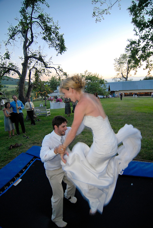 A bride and groom go for a post-wedding bounce on a trampoline in Montana.