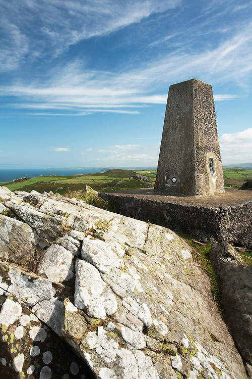 Trig point at Garn Fawr fort looking towards Strumble Head on the Pembrokeshire coast, Wales, Uk