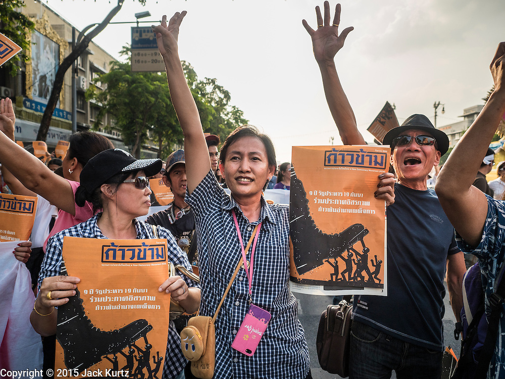 "19 SEPTEMBER 2015 - BANGKOK, THAILAND:  Anti-coup protestors march to Democracy Monument during a rally against the military government. The sign they are carrying says, ""Let's Declare Victory and Step Over Dictatorial Power."" Hundreds of people protested against Thailand's military dominated government Saturday. The protest started with seminar about the 2006 coup that deposed popularly elected former Prime Minister Thaksin Shinawatra. After the seminar activists marched from Thammasat University to Democracy Monument, about 1 mile. Political gatherings of more than 5 people are banned by Thailand's military government and police tried to dissuade the protestors from finishing their march. Protestors ignored the police, who then stood by and watched but made no effort to intervene. At Democracy Monument protestors laid flowers and made speeches against the military. It was the largest anti-coup protest in Bangkok in more than a year.    PHOTO BY JACK KURTZ"