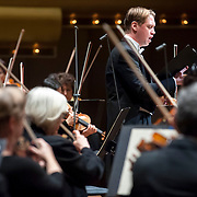 """November 21, 2013 - New York, NY : Tenor Michael Slattery, standing, and accompanies the New York Philharmonic in Bejamin Britten's """"Serenade for Tenor, Horn, and Strings, Op. 31 (1943)"""" at Avery Fisher Hall at Lincoln Center on Thursday night. Slattery made his NY Phil debut as a last-minute substitution for tenor Paul Appleby, who withdrew due to illness. CREDIT: Karsten Moran for The New York Times"""