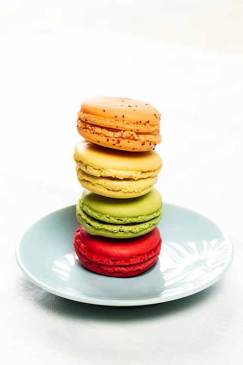 Colorful french pastries stacked in a blue plate.