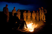 Members of US and Dutch coalition forces warm themselves by a trash fire while waiting for a helicopter flight at Forward Operations Base Diablo on Saturday, March 31, 2007.