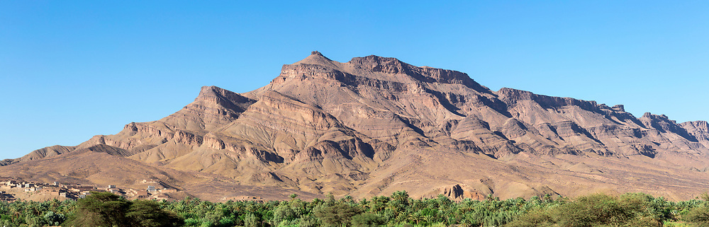 Landscape of the distinctive windswept synclinal rock formations of Jbel (Mount) Kissane mountain, Draa Valley, Southern Morocco, 2015-06-13.<br /><br />The mountain range dominates the eastern landscape of the sleepy oasis palmery town of Agdz with it's charateristic rock formations and several peaks (the highest reaching 1485metres).<br /><br />A variety of hues and tones can be seen in the rock at different times of the day and year, ranging from salmon pink to sun lit orange. <br /><br />Agdz is a small town located inbetween Ouarzazate and Zagora which offers a great glimpse into Southern Moroccan oasis palmery life, making a pefect overnight stop or lunch break off while traveling towards the southern Erg Chigaga region of the Sahara desert. <br />It played an important role in the trade between Marrakesh and Timbuktu via the old caravan route across the Sahara desert.
