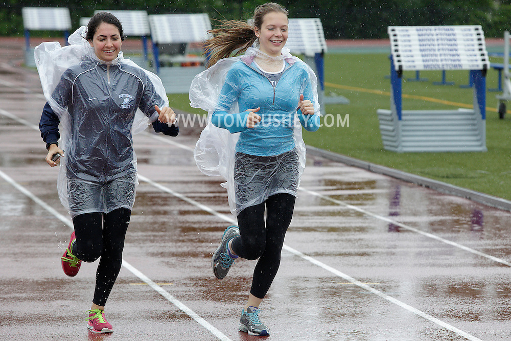 Margot Corper and Charlotte Diamond from the Nightingdale Bamford School in Manhattan warm up on the track at Middletown High School after the first day of the state track and field championships was postponed because of the wet weather on Friday, June 7, 2013.