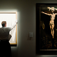 "London,UK - 7 June 2013: A Sotheby's employee holds a work entitled ""Concetto Spaziale Attese "" by Lucio Fontana (Est. £3.3-4.5 million) which stands next to El Greco's ?Christ on the cross? (Est. £3-5 million) during the preview of this summer auction at Sotheby's estimated at £100 million."