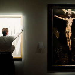 """London,UK - 7 June 2013: A Sotheby's employee holds a work entitled """"Concetto Spaziale Attese """" by Lucio Fontana (Est. £3.3-4.5 million) which stands next to El Greco's ?Christ on the cross? (Est. £3-5 million) during the preview of this summer auction at Sotheby's estimated at £100 million."""