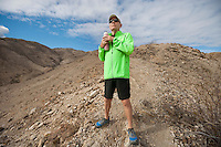 Determined senior man holding water bottle while standing on mountain