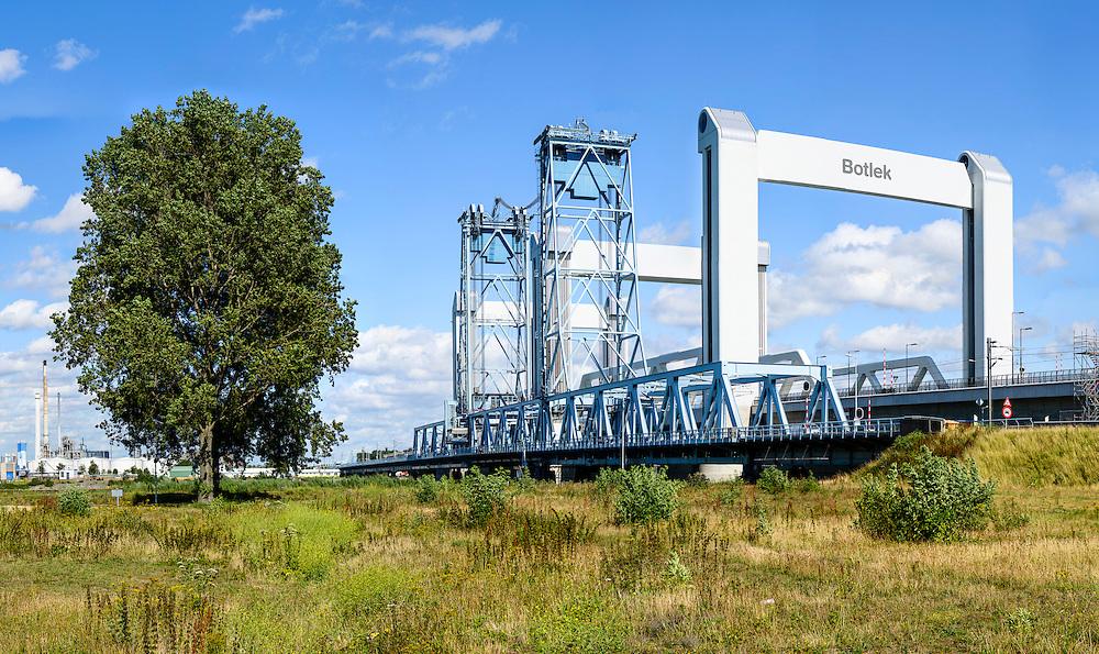 Nederland, Zuid-Holland, Rotterdam, 19-07-2015; Nieuwe en oude Botlekbrug. Kenmerkend voor beide hefbruggen zijn de heftorens. De nieuwe brug is niet alleen breder maar ook hoger dan de oude brug en door de groter hoogte boven het water kan het scheepvaartverkeer makkelijker passeren (waardoor de brug minder vaak geopend hoeft te worden).<br /> The new Botlek bridge next to the old construction.<br /> The bridge over the Oude Maas is a vertical-lift bridge or lift bridge.<br /> copyright foto/photo Siebe Swart