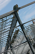 A worker from Ferguson Steel Erection, Inc., Greenville, PA, attaches a beam to the frame of an addition at Crosstex International in Sharon, PA on March 11, 2009.