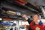 Nederland, Malden, 25-3-2010Een automonteur in een garage die gespecialiseerd is in Peugeot en Citroen vervangt een deel van de uitlaat.Foto: Flip Franssen/Hollandse Hoogte