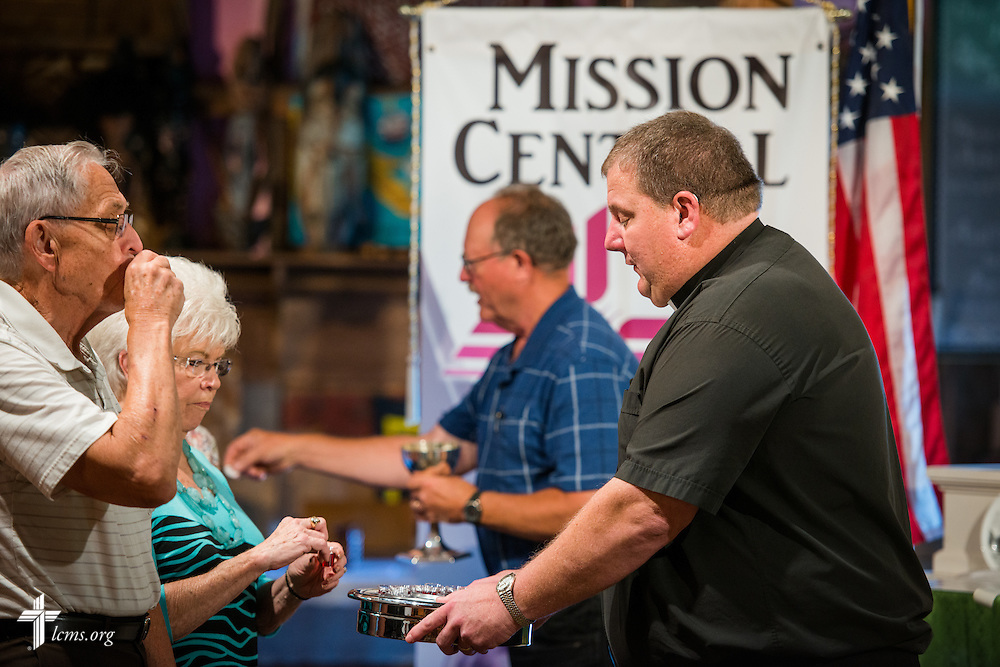 The Rev. David Lyons, pastor of St. Paul Lutheran Church in Schaller, Iowa, communes members of his congregation in the sanctuary and mission museum during worship at Mission Central on Sunday, July 19, 2015, in Mapleton, Iowa. LCMS Communications/Erik M. Lunsford