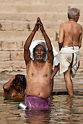 Indian Hindu man bathing and praying in the River Ganges by Kshameshwar Ghat in holy city of Varanasi, India