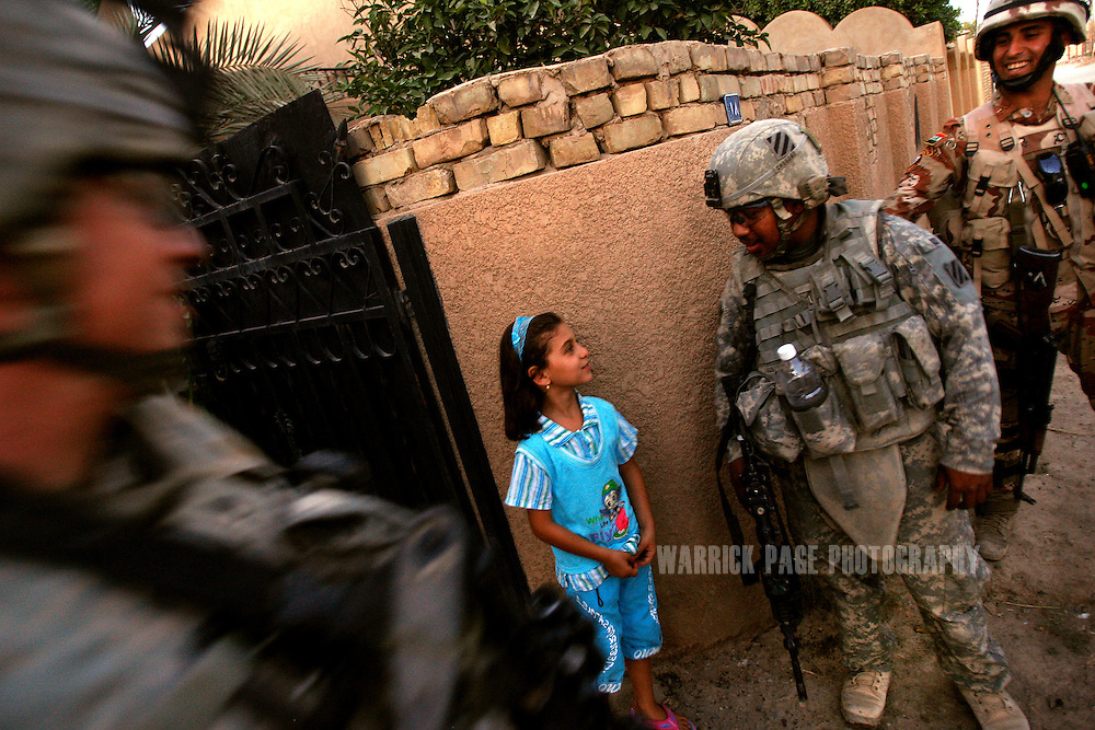BAGHDAD, IRAQ - JUNE 25: Sgt. Staisman Sadang (2-R) talks with Iraq girl, Noor (8) (2-L), as soldiers with Alpha Company, 4th Battalion, 6th Armoured, 4th Brigade, 3rd Infantry Division, search homes during a patrol with Iraqi forces in the suburb of Sadiyah, June 25, 2008, Baghdad, Iraq. Neighbourhoods like Sadiyah became a battleground for Shiite militias and Sunni extremists after the bombing of the Golden Mosque in Samarra in 2006. Tens of thousands of people were either forced out of their homes or fled the violence to neigbouring countries or other parts of Iraq. Now predominantly Shiite, Sadiyah is being used as a test case by the Iraqi government to encourage the millions who have fled - many of which have the skills and money to rebuild the country. Since early 2008, Iraq's security situation has improved with oil production is increasing, record government surplus and easing sectarian tensions. (Photo by Warrick Page)
