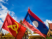16 JUNE 2016 - PAKSE, CHAMPASAK, LAOS: The Communist hammer and sickle flag next to the Lao flag on a street in Pakse. Laos is still a one party Communist country. Pakse is the capital of Champasak province in southern Laos. It sits at the confluence of the Xe Don and Mekong Rivers. It's the gateway city to 4,000 Islands, near the border of Cambodia and the coffee growing highlands of southern Laos.      PHOTO BY JACK KURTZ