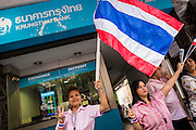 """20 DECEMBER 2013 - BANGKOK, THAILAND:  Bank workers stand on the sidewalk in front of their bank and watch an anti-government protest on Silom Road. Many of the protestors are members of the Thai middle class, and workers in the offices and banks along Silom Road. Thousands of anti-government protestors, supporters of the so called Peoples Democratic Reform Committee (PRDC), jammed the Silom area, the """"Wall Street"""" of Bangkok, Friday as a part of the ongoing protests against the caretaker government of Yingluck Shinawatra. Yingluck dissolved the Thai Parliament earlier this month and called for national elections on Feb. 2, 2014. The protestors want the elections postponed and the caretaker government to step down. The Thai election commission ruled Friday that the election would go on dispite the protests.         PHOTO BY JACK KURTZ"""