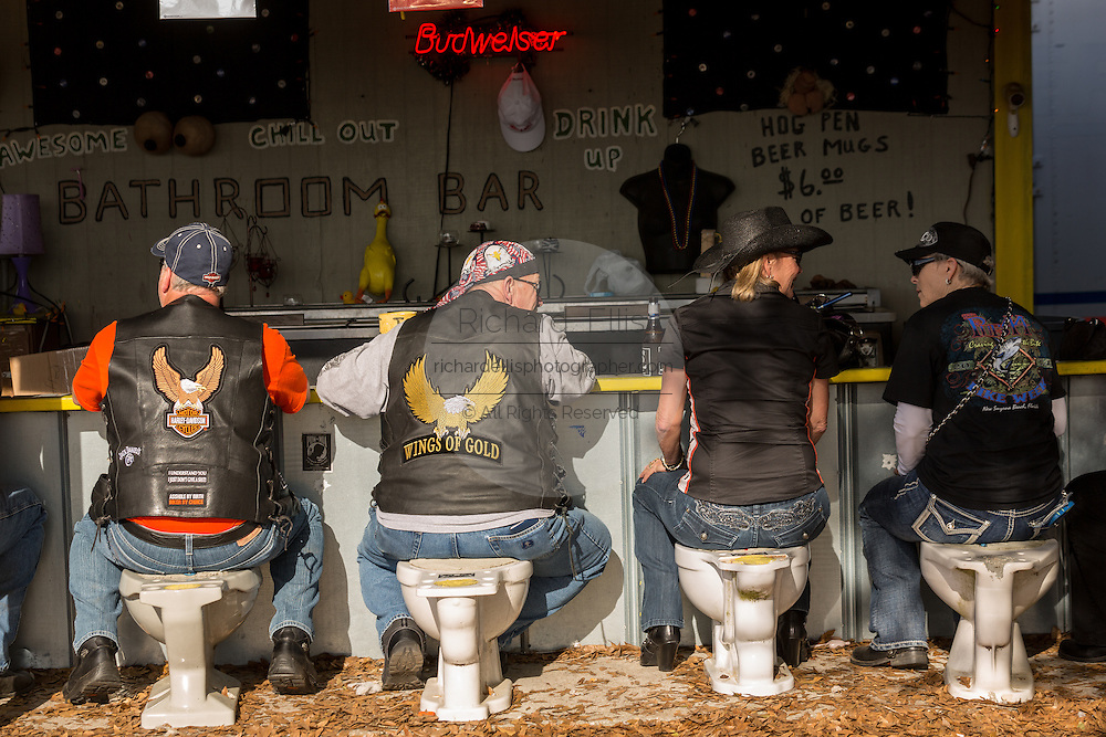 Bikers sit on toilet seats at the Hog Pen bathroom bar during the 74th Annual Daytona Bike Week March 8, 2015 in Daytona Beach, Florida. More than 500,000 bikers and spectators gather for the week long event, the largest motorcycle rally in America.