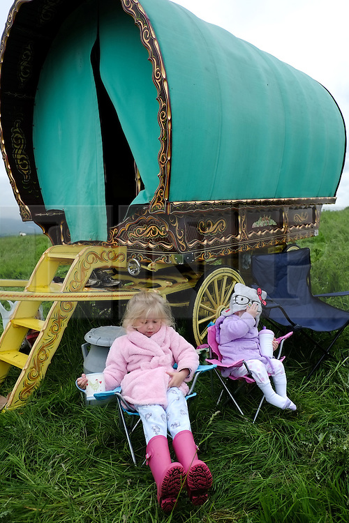 © Licensed to London News Pictures. <br /> 05/06/2014. <br /> <br /> Appleby, Cumbria, England<br /> <br /> Hayley Price (L) 4, and her sister Candice (16 months) sit outside their family bow top as gypsies and travellers gather during the annual horse fair on 5 June, 2014 in Appleby, Cumbria. The event remains one of the largest and oldest events in Europe and gives the opportunity for travelling communities to meet friends, celebrate their music, folklore and to buy and sell horses.<br /> <br /> The event has existed under the protection of a charter granted by King James II in 1685 and it remains the most important event in the gypsy and traveller calendar.<br /> <br /> Photo credit : Ian Forsyth/LNP