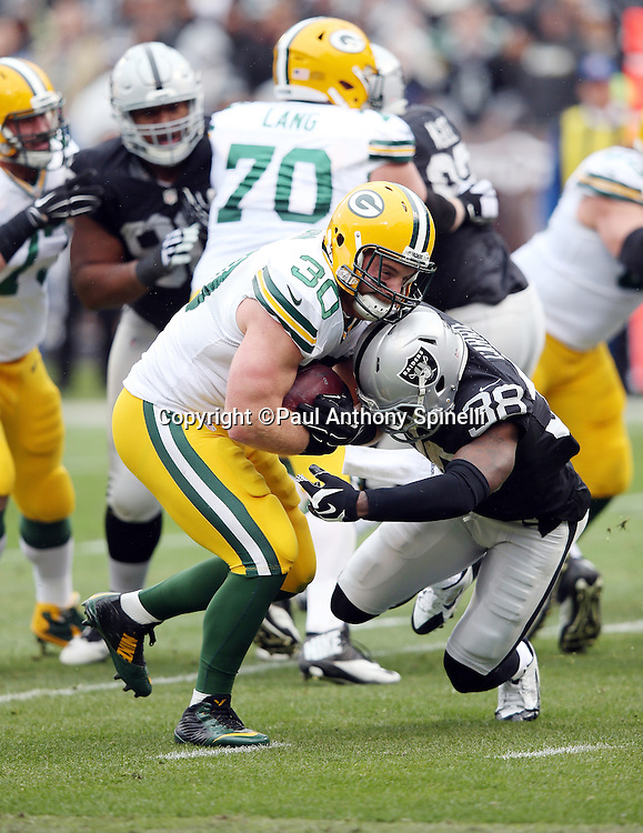 Green Bay Packers fullback John Kuhn (30) breaks a tackle attempt by Oakland Raiders strong safety T.J. Carrie (38) as he runs for a 5 yard touchdown good for a 7-0 first quarter Packers lead during the 2015 week 15 regular season NFL football game against the Oakland Raiders on Sunday, Dec. 20, 2015 in Oakland, Calif. The Packers won the game 30-20. (©Paul Anthony Spinelli)