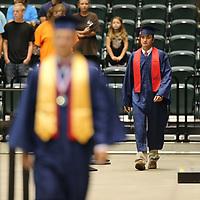 Coleton Ausbern makes his way to his seat as the Nettleton High School seniors begin their graduation ceremony Saturday morning.