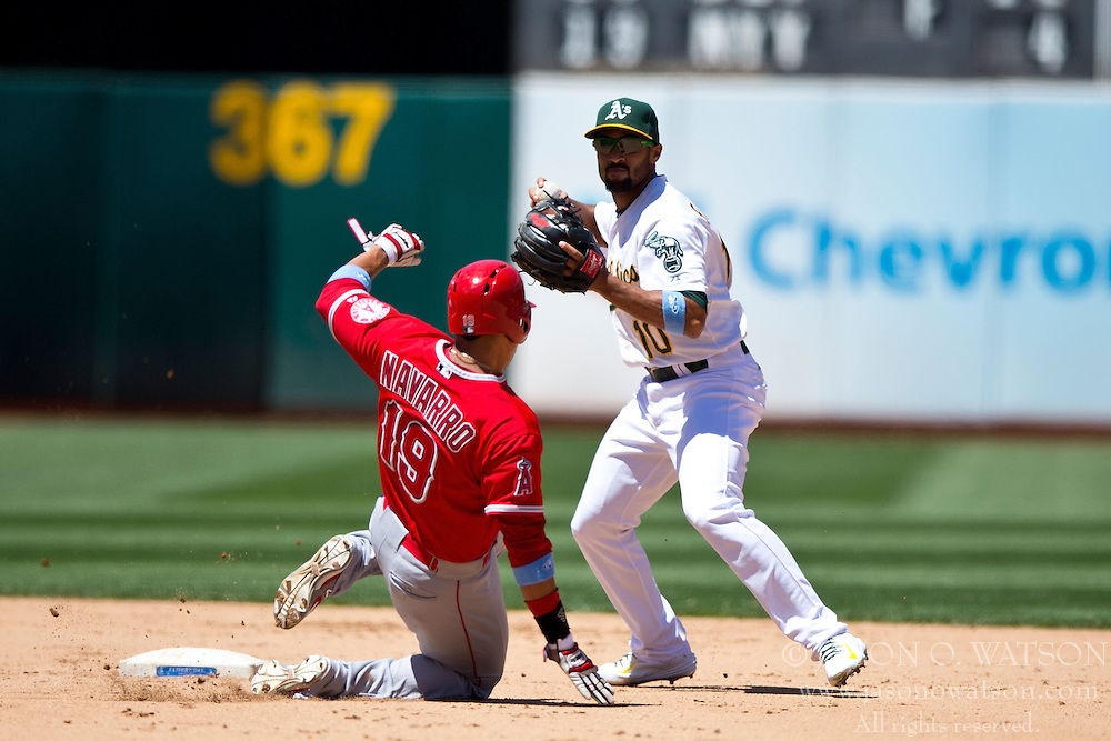 OAKLAND, CA - JUNE 21:  Marcus Semien #10 of the Oakland Athletics completes a double play over Efren Navarro #19 of the Los Angeles Angels of Anaheim during the fifth inning at O.co Coliseum on June 21, 2015 in Oakland, California. The Oakland Athletics defeated the Los Angeles Angels of Anaheim 3-2. (Photo by Jason O. Watson/Getty Images) *** Local Caption *** Marcus Semien; Efren Navarro