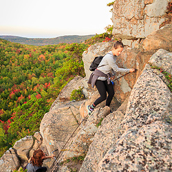 "Hikers climb ""The Beehive"" in fall in Maine's Acadia National Park."