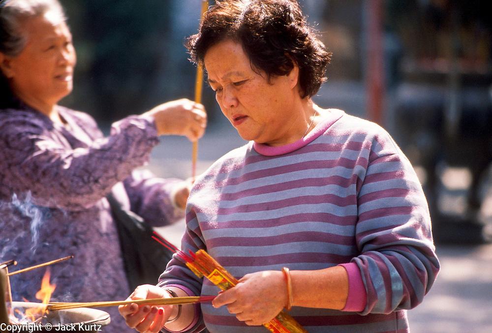01 DECEMBER 1988   - HONG KONG: Women light prayer sticks in a Buddhist temple in Hong Kong. PHOTO © JACK KURTZ  WOMEN  RELIGION