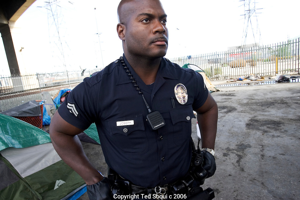 LAPD Senior Lead Officer Deon Joseph in front of a small homeless encampment under LA's Sixth Street Bridge.