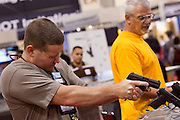 16 MAY 2009 -- PHOENIX, AZ: A man aims a Heckler Koch handgun in the HK booth at the NRA convention in Phoenix. About 60,000 people were expected to attend the trade show at the 138th annual National Rifle Association Annual Meeting in the Phoenix Convention Center in Phoenix, AZ. Photo by Jack Kurtz / ZUMA Press