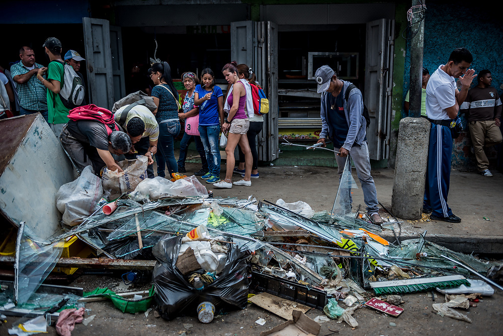 CARACAS, VENEZUELA - APRIL 21, 2017:  People pick through the debris from a butcher shop that was one of over a dozen stores looted late last night in El Valle, a working class neighborhood in Caracas. The streets of Caracas erupted into a night of riots, looting and clashes with National Guardsmen as anger from two days of pro-democracy protests spilled into unrest in working class neighborhoods and slums. Shots rang out throughout the night in El Valle, a neighborhood of mixed loyalties, as armored vehicles struggled to contain crowds of looters. At one point during the night, clashes became so heavy that a nearby children's hospital was evacuated after the ward filled with tear gas. The government said they were responding to an attack on the hospital by opposition protestors.  PHOTO: Meridith Kohut