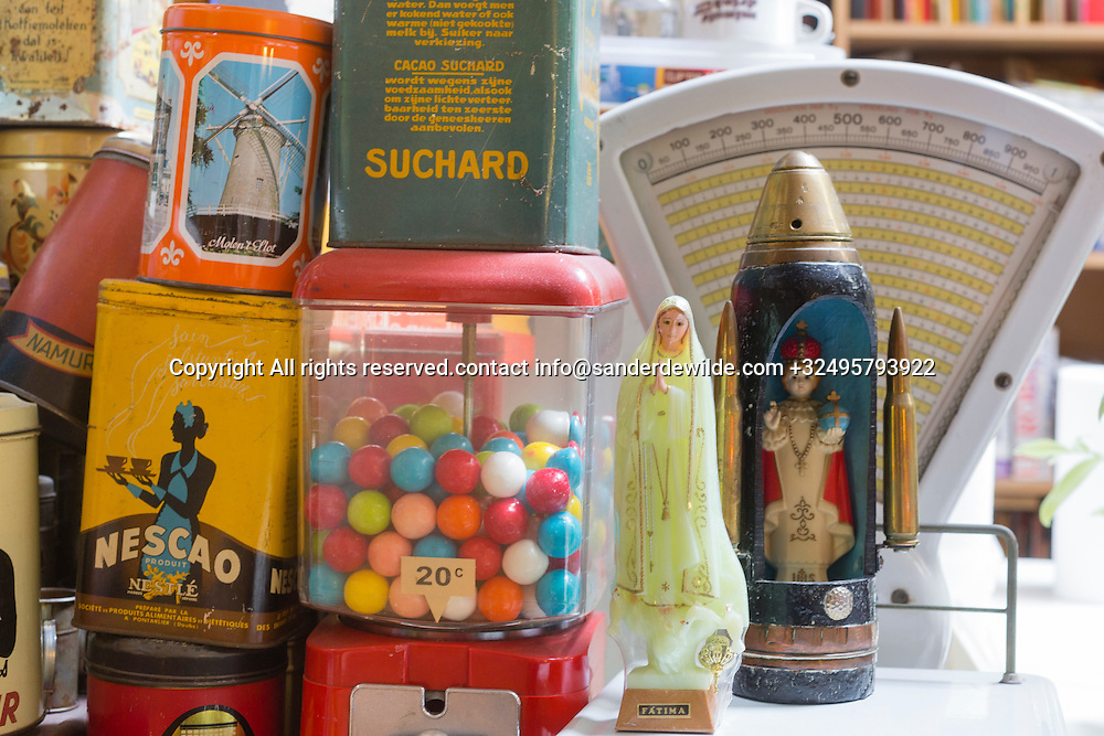 Brussels, Belgium 29 August 2014. In the studio of Johan De Moor, famous Belgian cartoonist and son of Bob De Moor, a large collection of strange objects like a fatima, candy machine,old tin cans, a scale and an angel in a WWI shell . © Sander de Wilde pour M le magazine du Monde