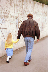 Man leading young girl by hand walking down the street,