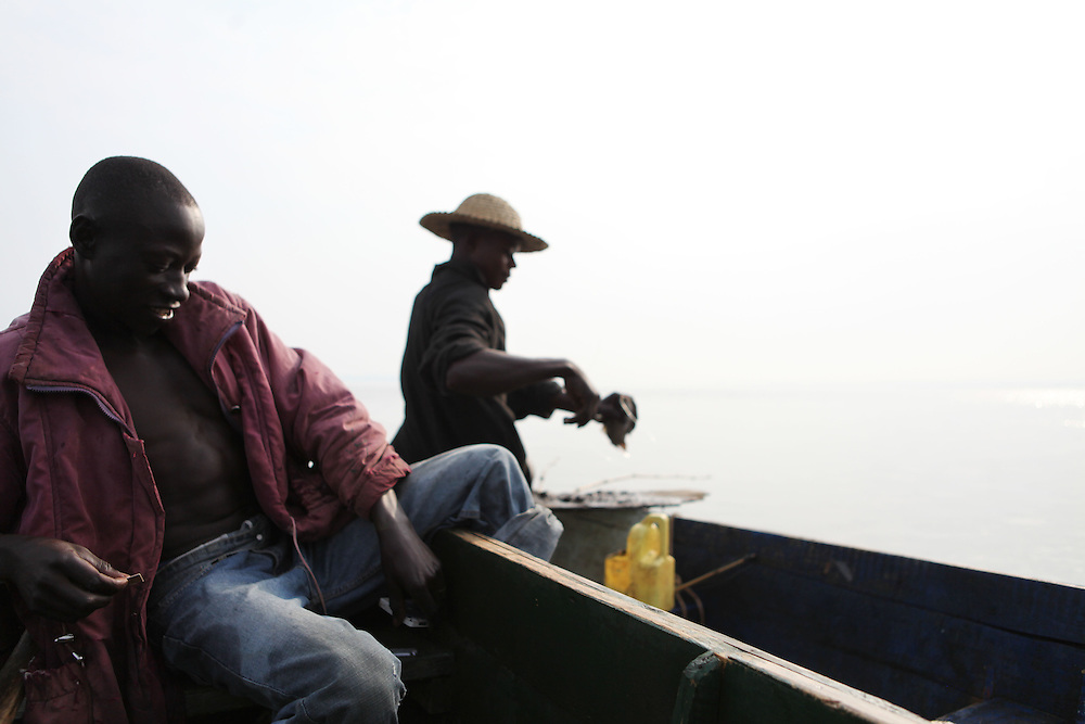 Augustino Ssekisaka (left) and Siggando Francis frequently fish together on Lake Victoria. Here in Ggaba, a small town in southern Uganda that almost entirely subsists on the fishing industry, the locals have contributed to the dangerous overfishing of the lake despite strict regulations from Tanzania, Uganda, and Kenya. Fishermen continue to keep fish that are far below the required minimum weight and employ dymanite and poison.
