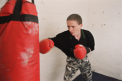 Resident using punch bag in homeless hostel for people with learning difficulties,