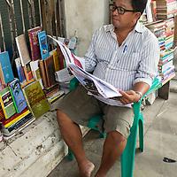 Myanmar (Burma). Yangon. A man selling books on the street reads his newspaper.