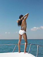 Young woman in bikini standing on bow of yacht looking at sea back view