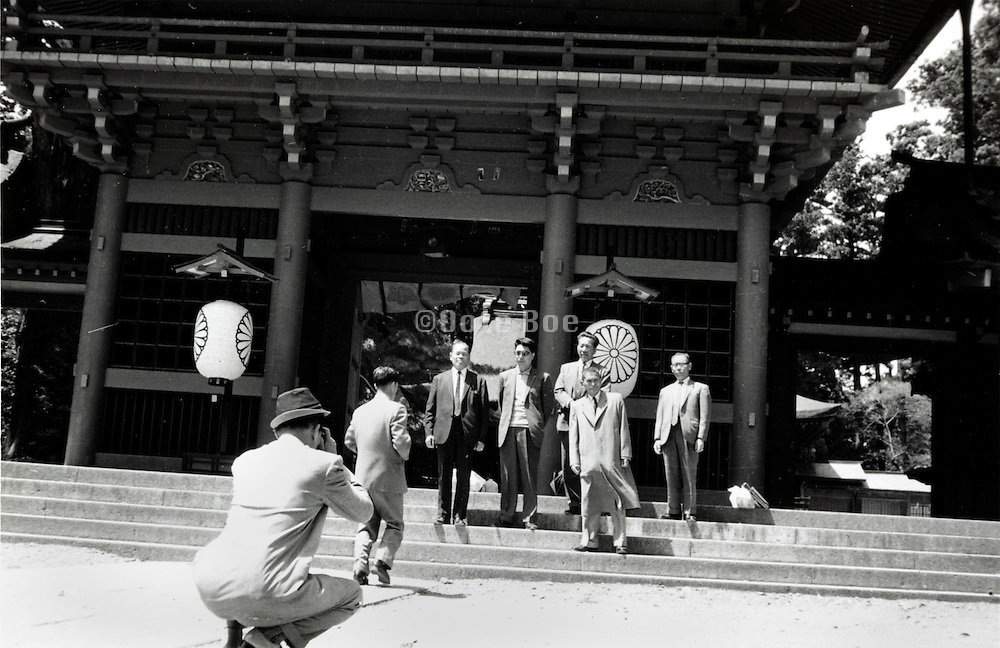 person taking picture of men standing in front of a temple gate Japan 1960s