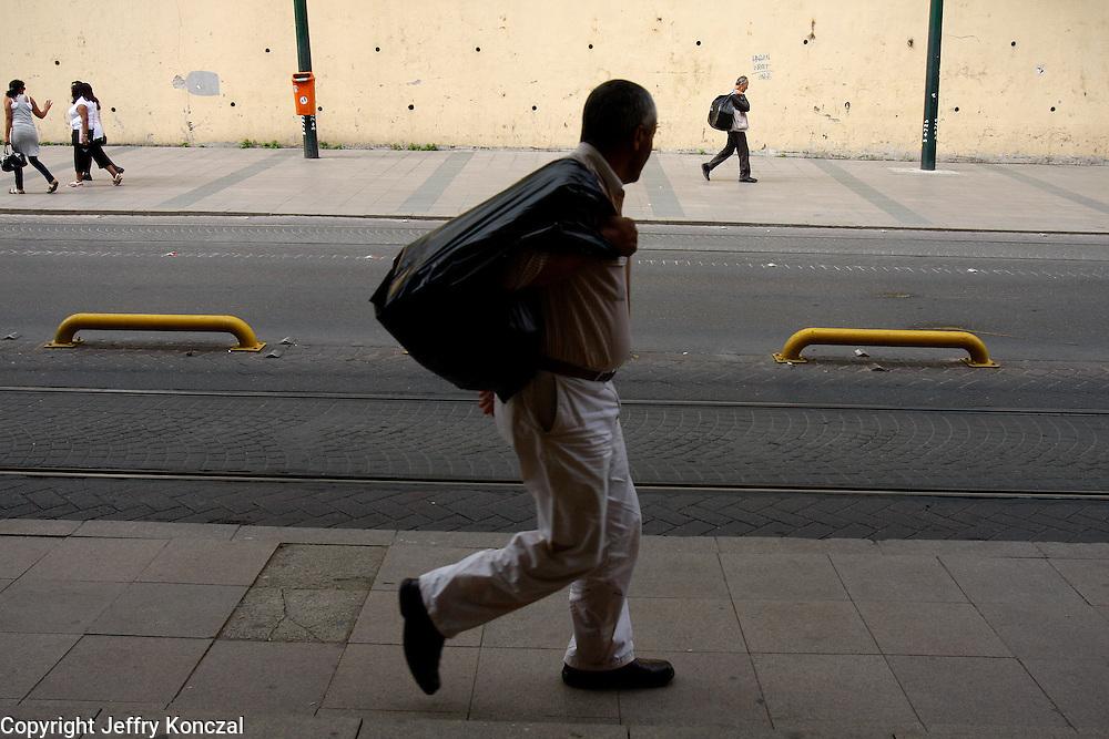 Two men on opposite sidewalks carry black trash bags over their shoulders in Istanbul, Turkey.